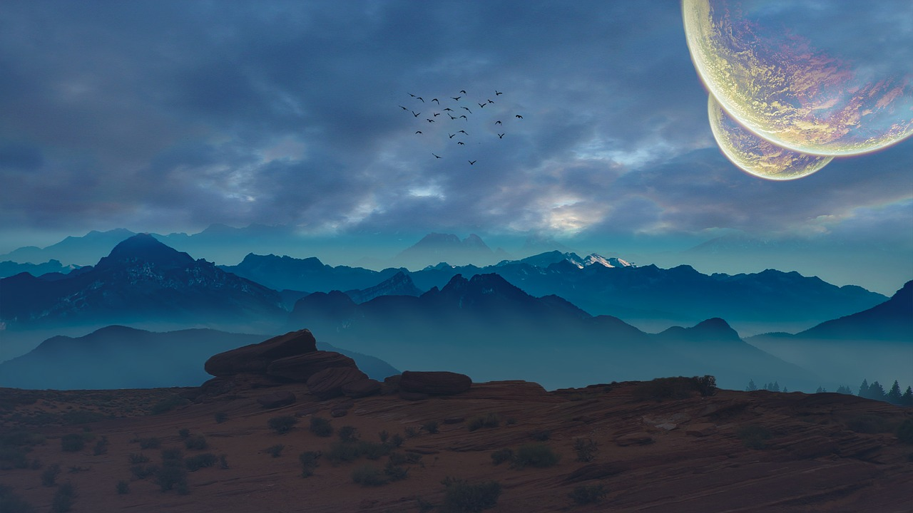 Poetry landscapre of sand and sandstones, layered with a background of mountains in blue mists, sky clouded and enormous planets taking up the sky. In the distant a flock of birds.