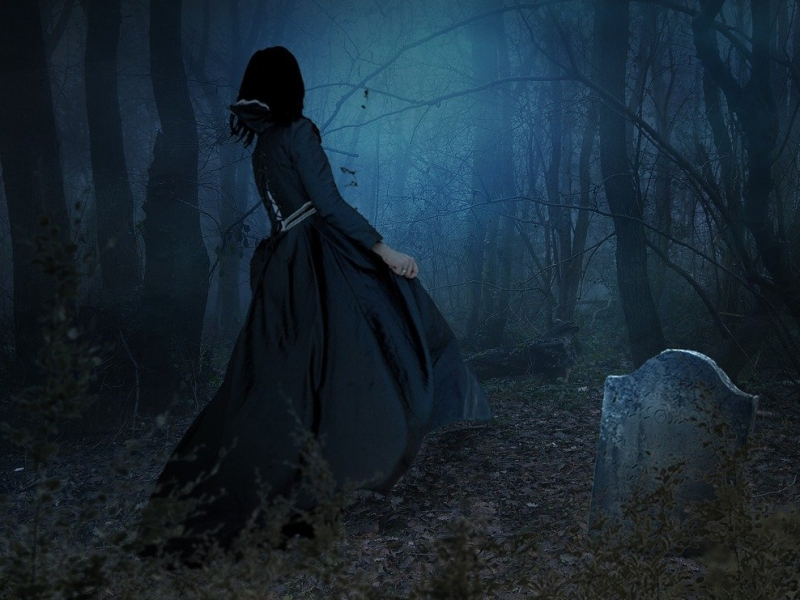 Poetry The back of a woman dressed in medieval midnight frock walking in a graveyard with a headstone jutting out from the ground in backdrop of a dark forest