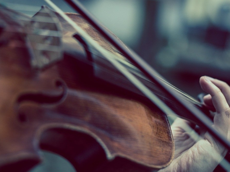 Poetry a hand holding up a violin and playing it in a blurred backdrop