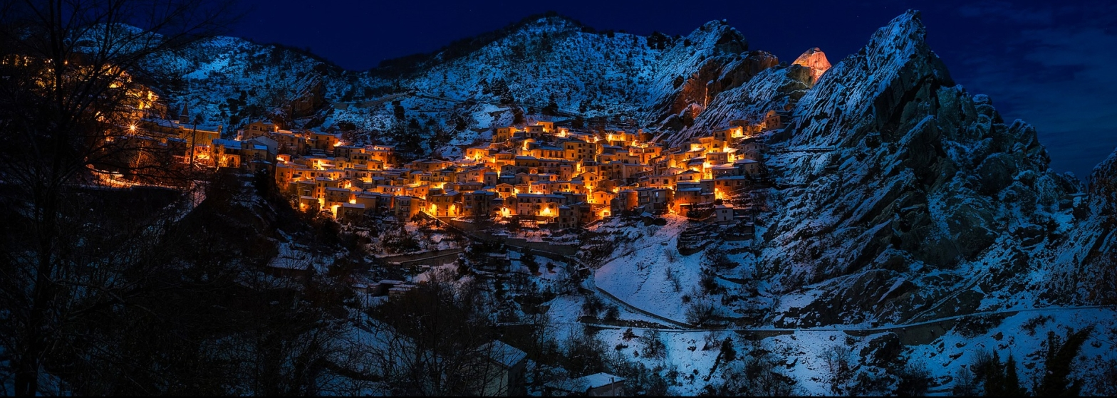 Poetry a cluster of houses lit in gold nestled within snowy mountains in the night sky
