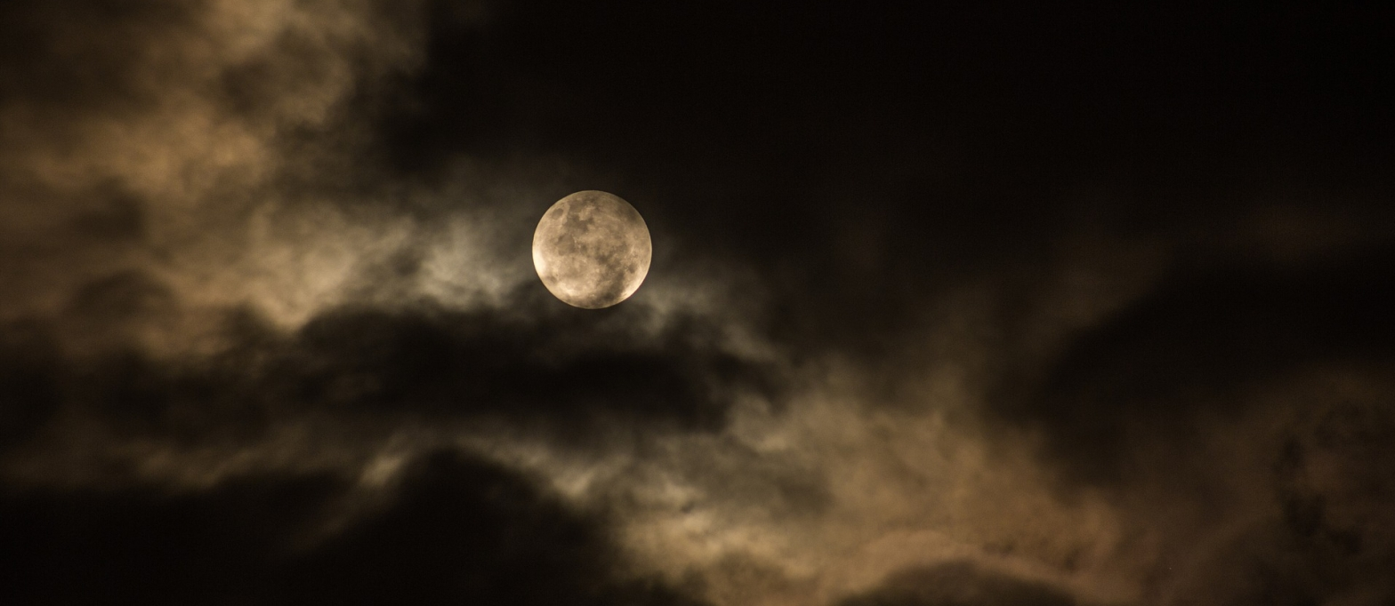 Poetry White shining full moon disc on a dark cloudy night sky