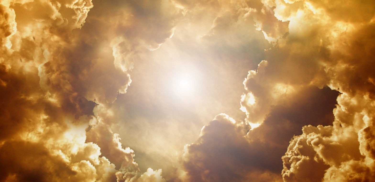 Poetry clouds lit in gold, copper and deep browns surrounding the sun