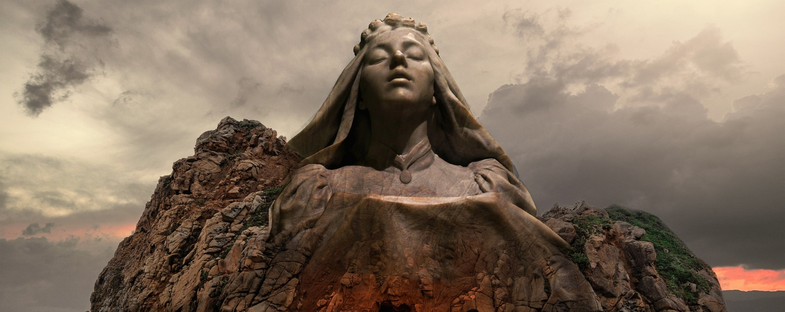 Poetry A stone goddess rising from the outcropping of a a rock jutting out from the Earth in a backdrop of greying skies