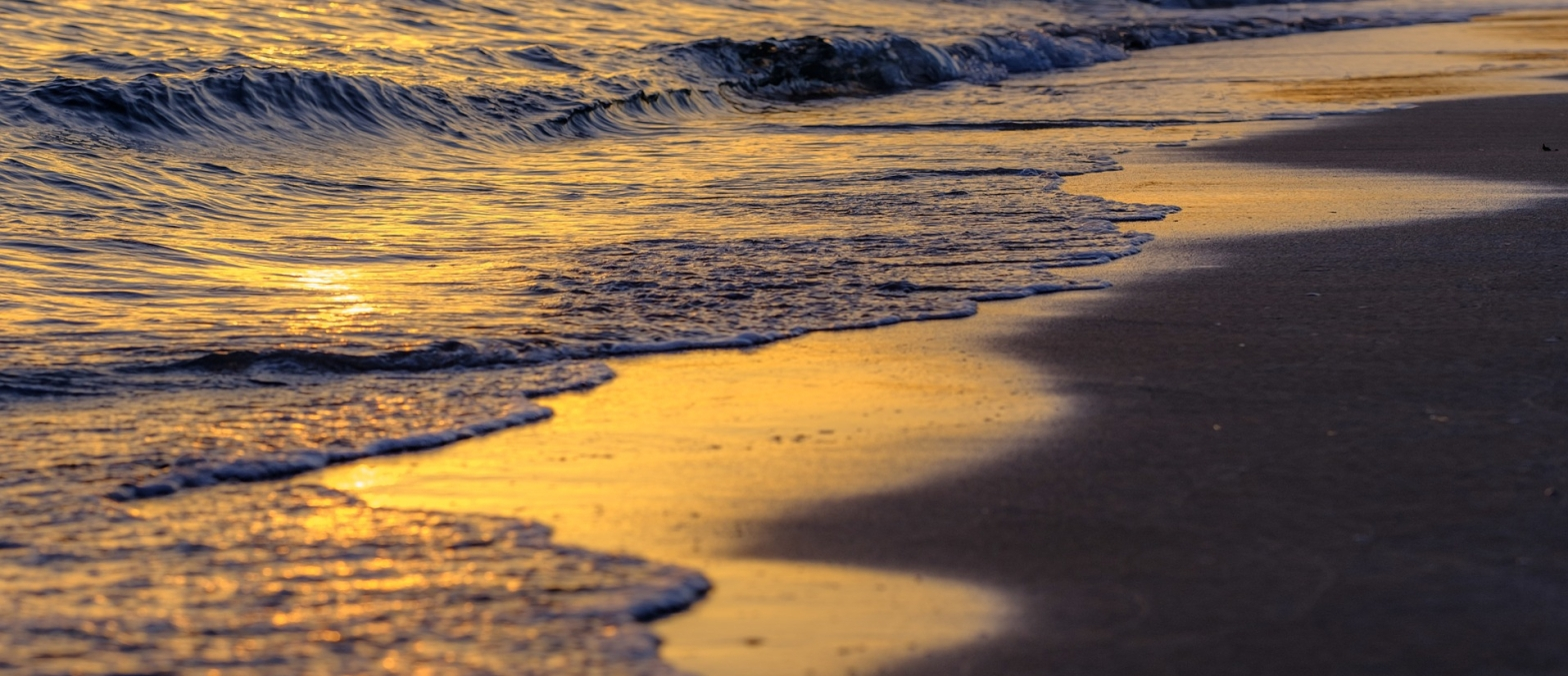 Poetry sea waves in sunset waving into the sands of the beach
